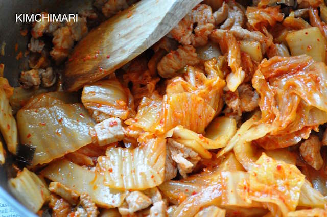 Kimchi and pork sauteeing in pot with wooden spoon