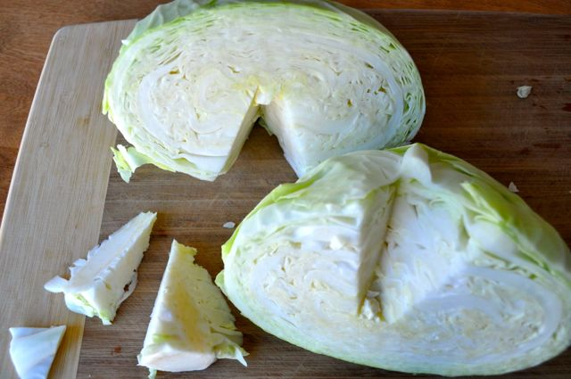Half cut cabbage with core cut out on cutting board