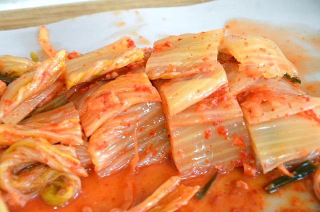 Cabbage Kimchi cut into slices on cutting board
