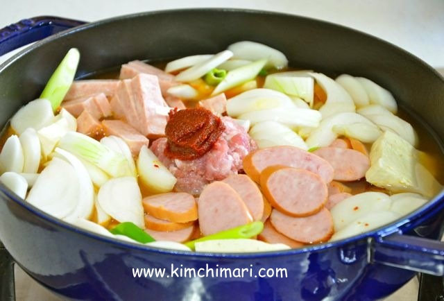 Budae Jjigae with all ingredients in pot with water added