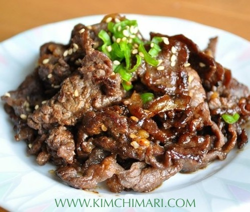 Bulgogi cooked and plated, garnished with chopped green onions on top