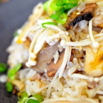 closeup of mushroom rice plated on black plate sprinkled with green onions