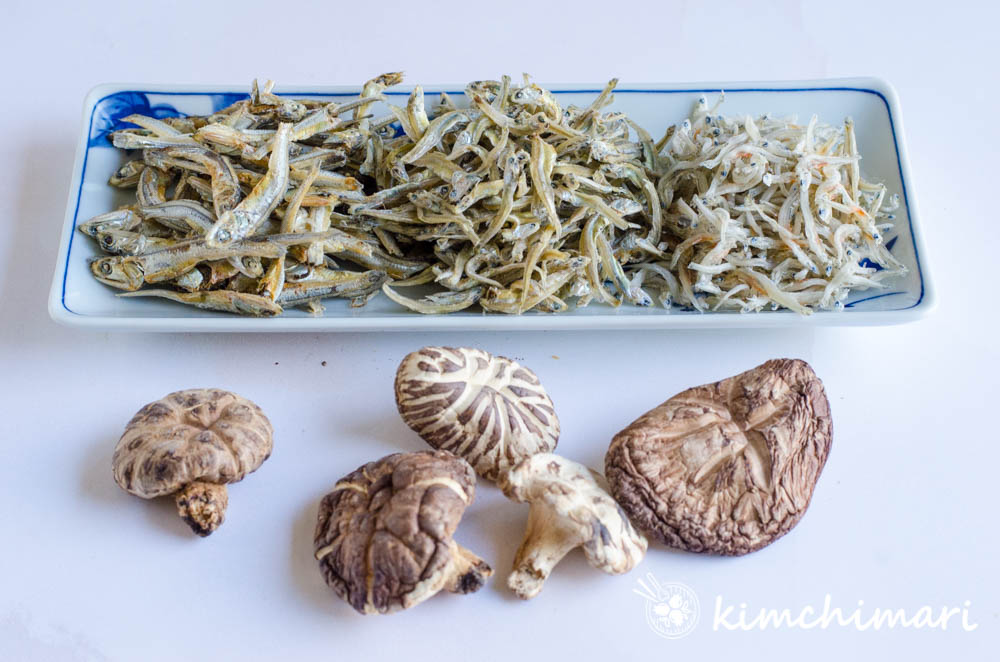 small and large korean dried anchovies and dried shitake mushrooms on white background