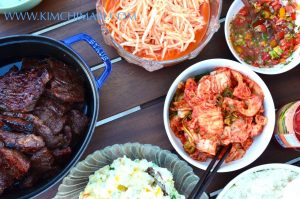 Korean BBQ party table with Kalbi, Radish Salad, Kimchi and Potato Salad