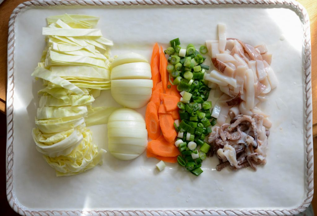 Ingredients for spicy squid stir fry : cabbage, onions, carrots, green onions and squid