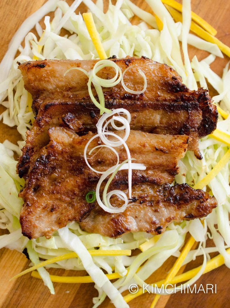 Grilled miso pork belly served on cabbage slaw and green onions