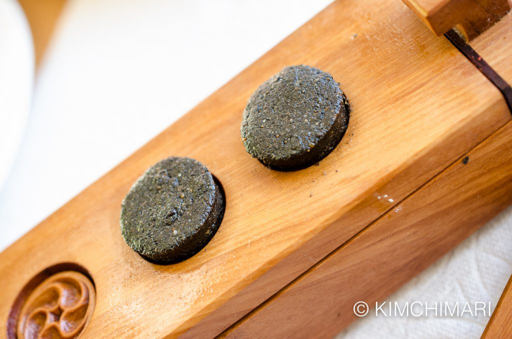 sesame tea cookie sticking out from dasik pan