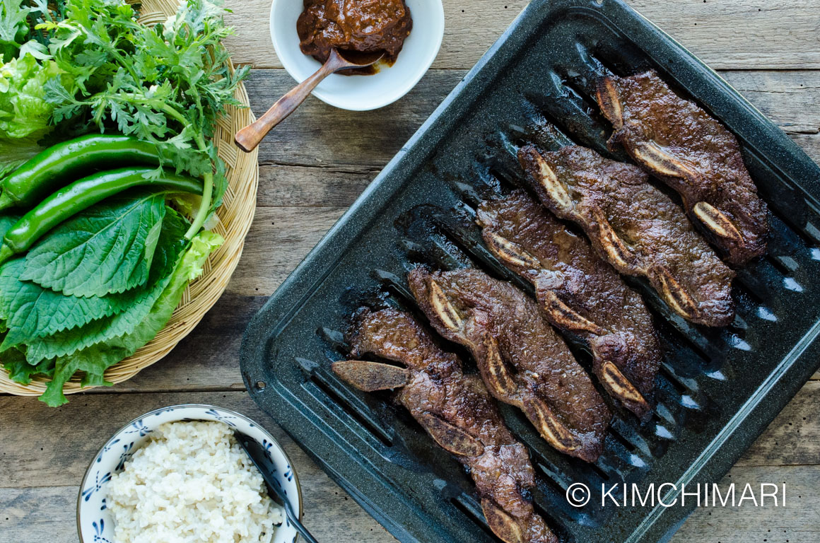 top view of Kalbi Short Ribs on grill pan, ssamjang in a bowl, rice and plate of ssam greens