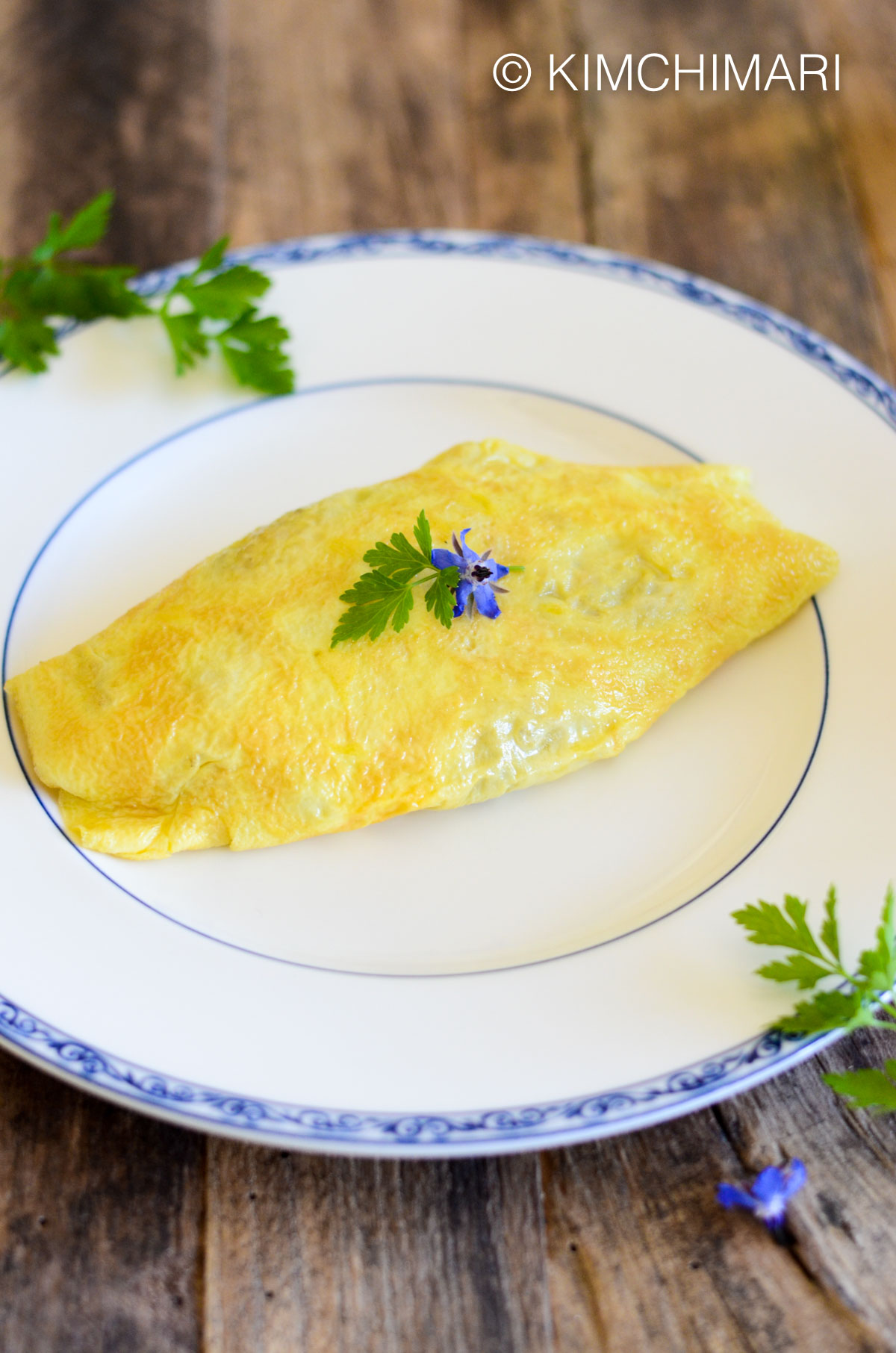 omurice served on white plate garnished with parsely and boroage blossoms