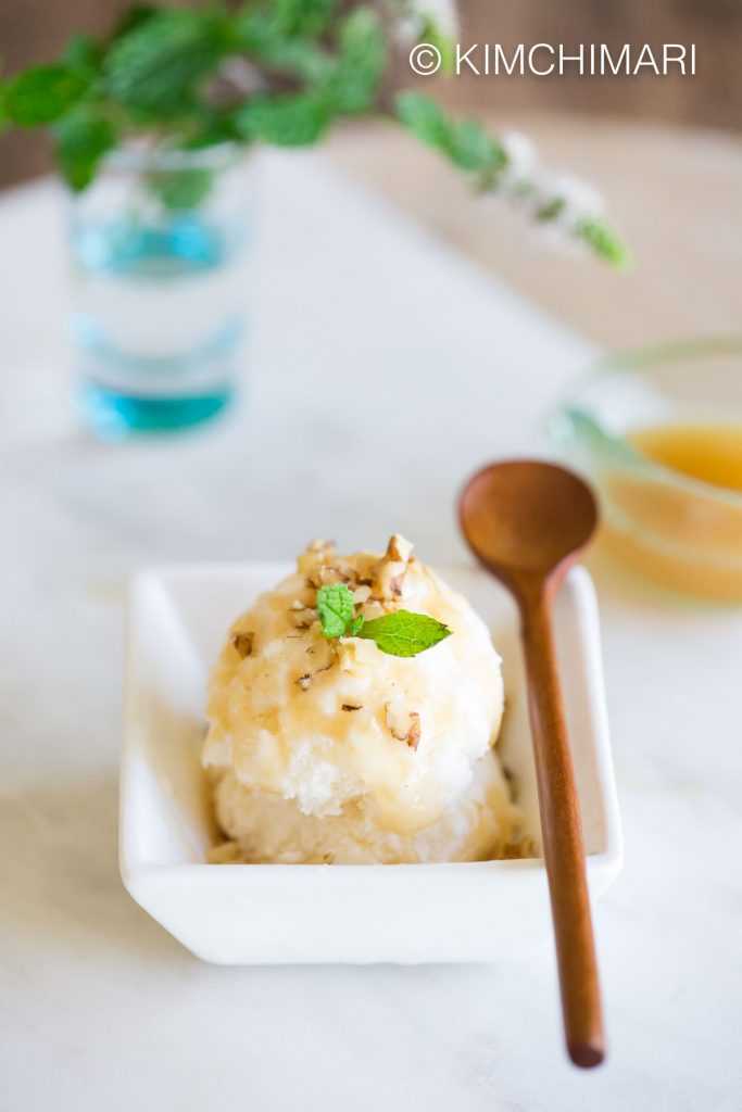Makgeolli Ice Cream served with chopped walnuts, makgeolli syrup and mint leaves