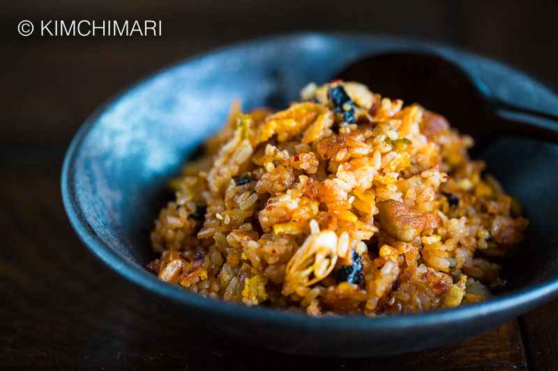 Kimchi Fried Rice in black bowl with wooden spoon