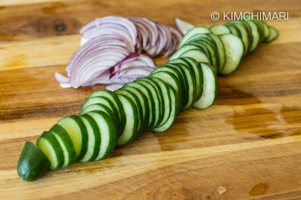 Japanese cucumber and red onions sliced on cutting board