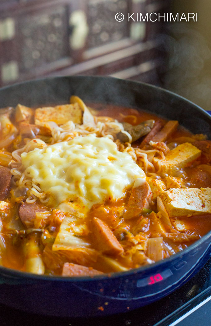 Side view of Budae Jjigae cooked in pot with steam escaping