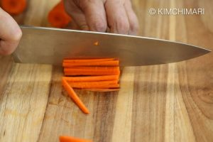 Julienning carrot with knife on cutting board