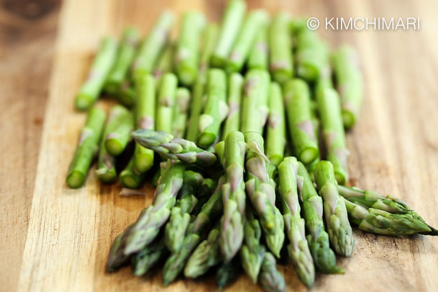 asparagus cut into 3rds on wooden cutting board