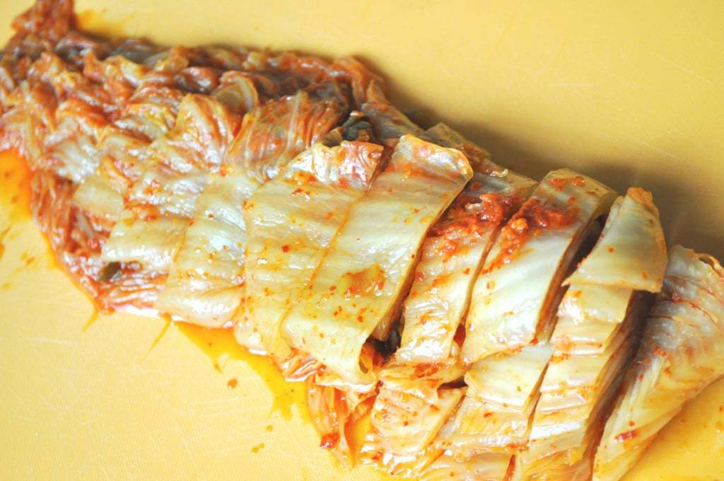 sour aged kimchi sliced on yellow plastic cutting board