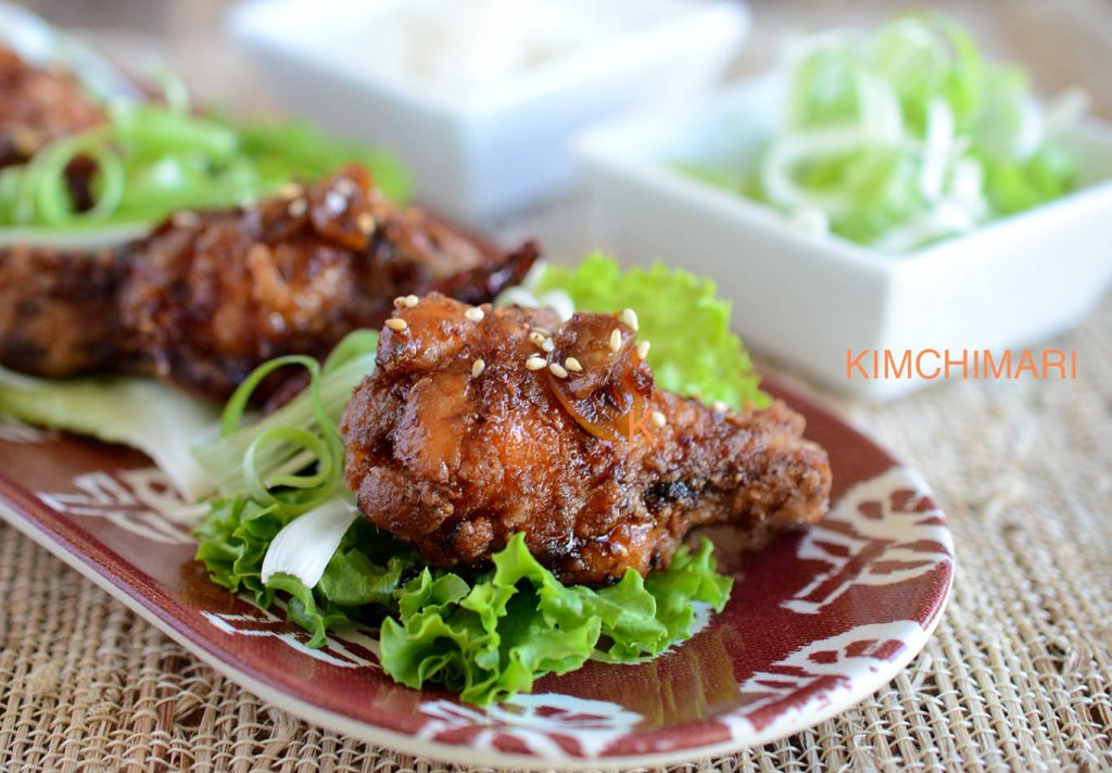 Korean Fried Chicken plated with lettuce and green onions