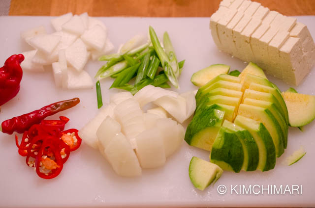 cutting board with cut onion, radish, green onion, tofu, zucchini and peppers for pollock roe stew