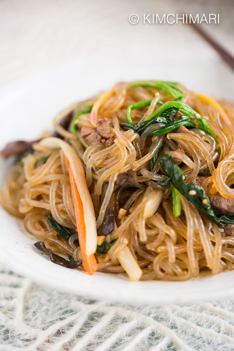 Close up of Japchae with beef and vegetables plated on white plate