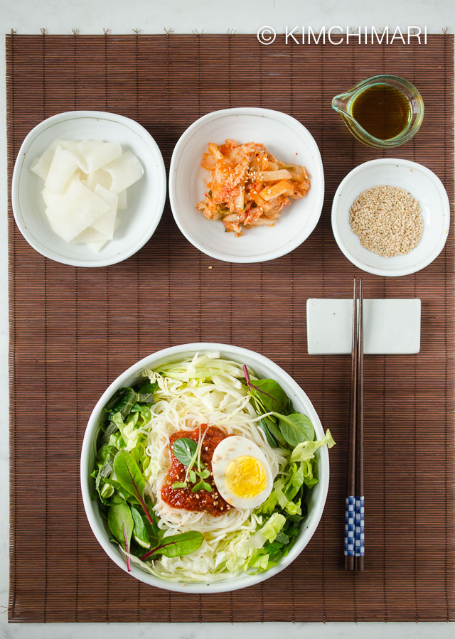 Table Top view of bibim guksu bowl with chopsticks on the side and kimchi and pickled radish as side dishes