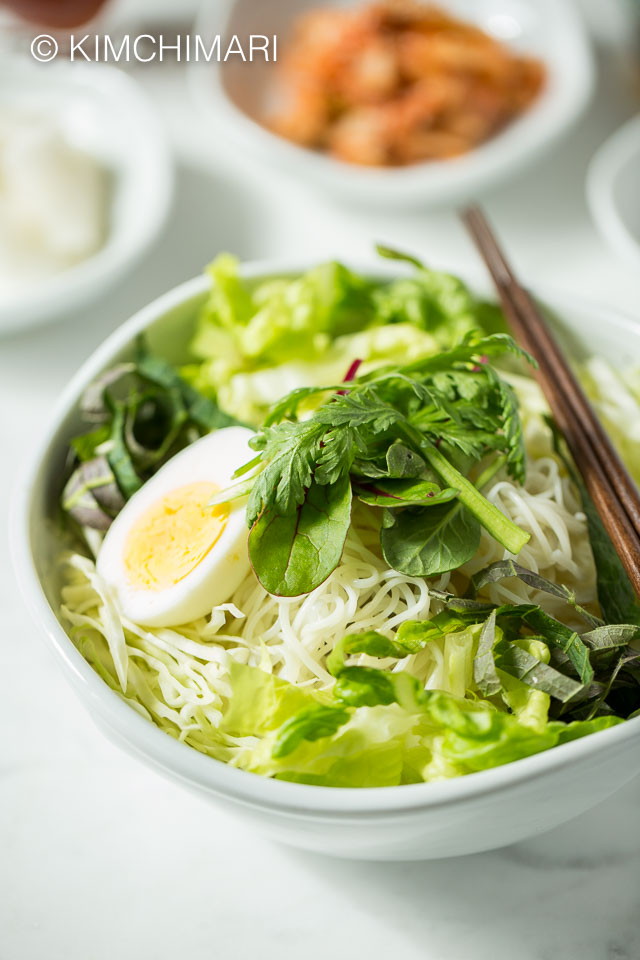 Bowl of bibim guksu served with vegetables and egg but before bibim sauce is added