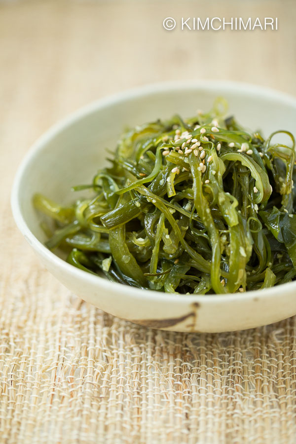 Cooked Seaweed side dish plated on light cream colored shallow dish, sprinkled with sesame seeds