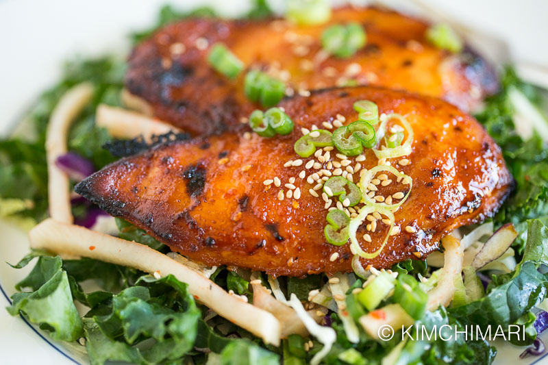 baked chicken breast on top of kale salad mix, topped with green onions