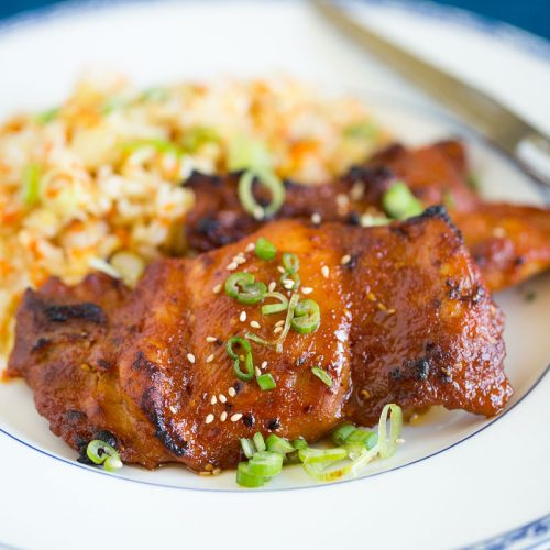 baked spicy chicken thighs plated with simple carrot fried rice