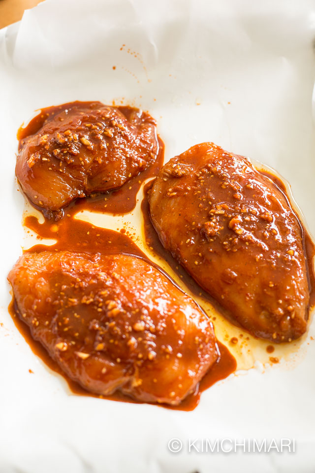 marinated chicken breasts on parchment paper lined tray