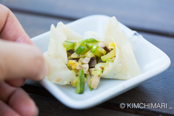 dumpling is torn open to show the vegetable stuffing inside