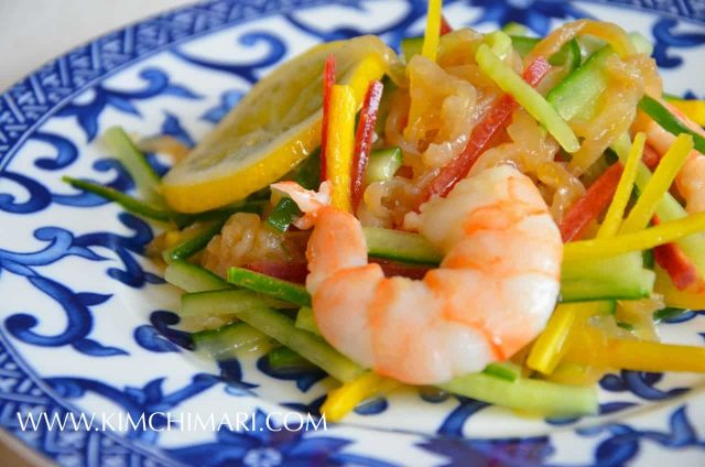 jellyfish salad with cucumbers lemon shrimp served on plate with blue designs