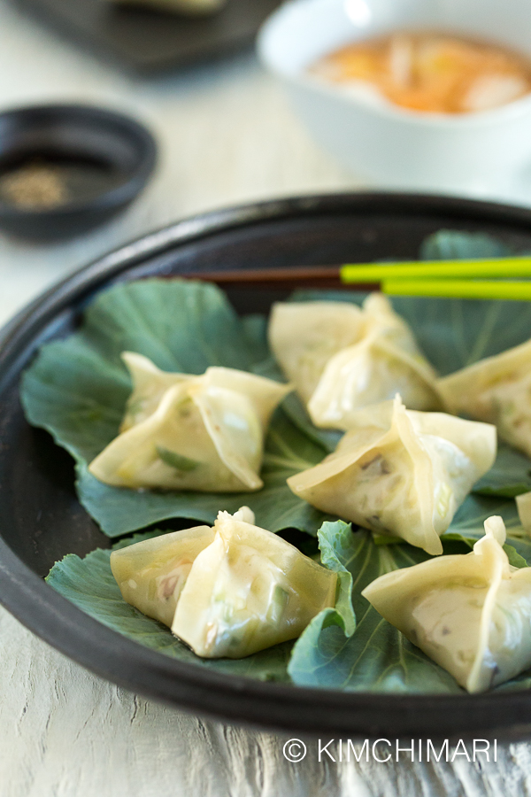 vegetarian dumplings served on black plate with dipping sauce in the background