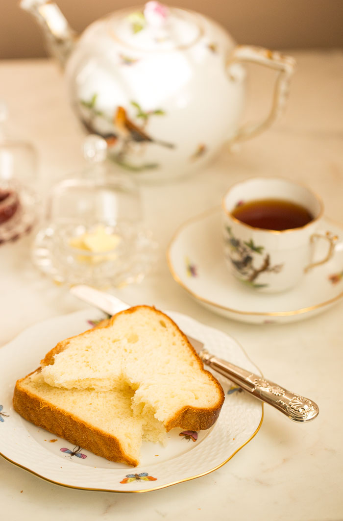 tea served in cup with slice of bread, butter and jam