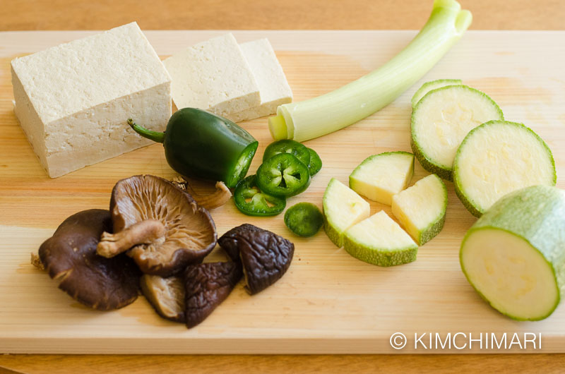 vegetable ingredients on cutting board - tofu, zucchini, green onions, shitake mushrooms and Jalapeno peppers