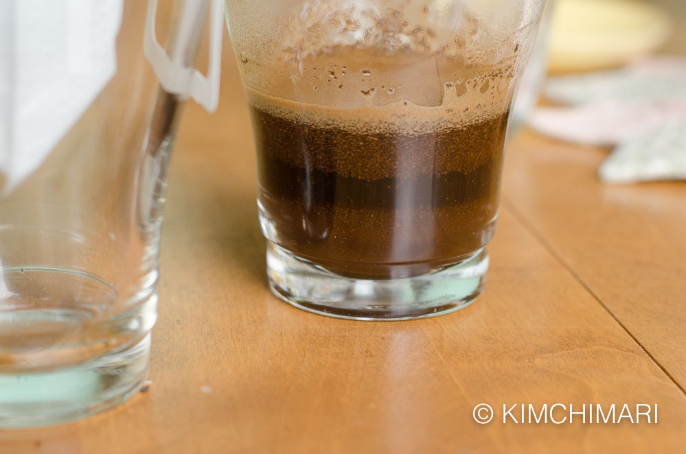 coffee grounds mixed with water in glass cup