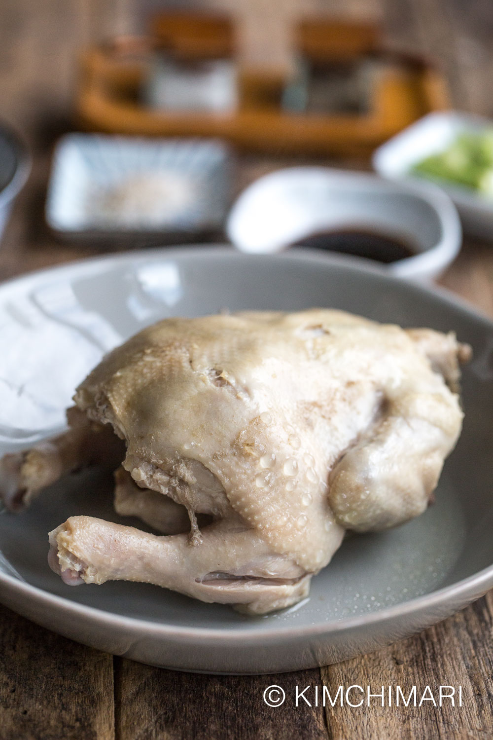 cooked whole chicken on plate with sauces in the background