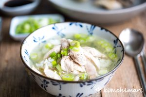 soup in bowl with chicken meat, rice and chopped green onions on top