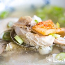 chicken soup in bowl with rice, chicken and kimchi piled on metal spoon
