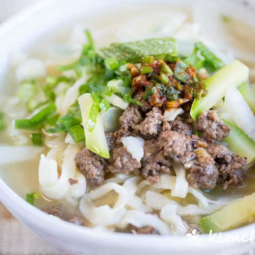 Finished Kalguksu in bowl topped with ground beef, green onions and fresh garlic with chopsticks on top