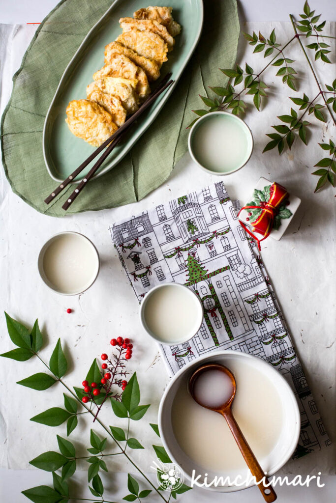 makgeolli served with fish jeon on a table setting with xmas decor