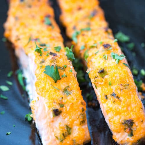 2 pieces of baked salmon with mayo masago on black plate