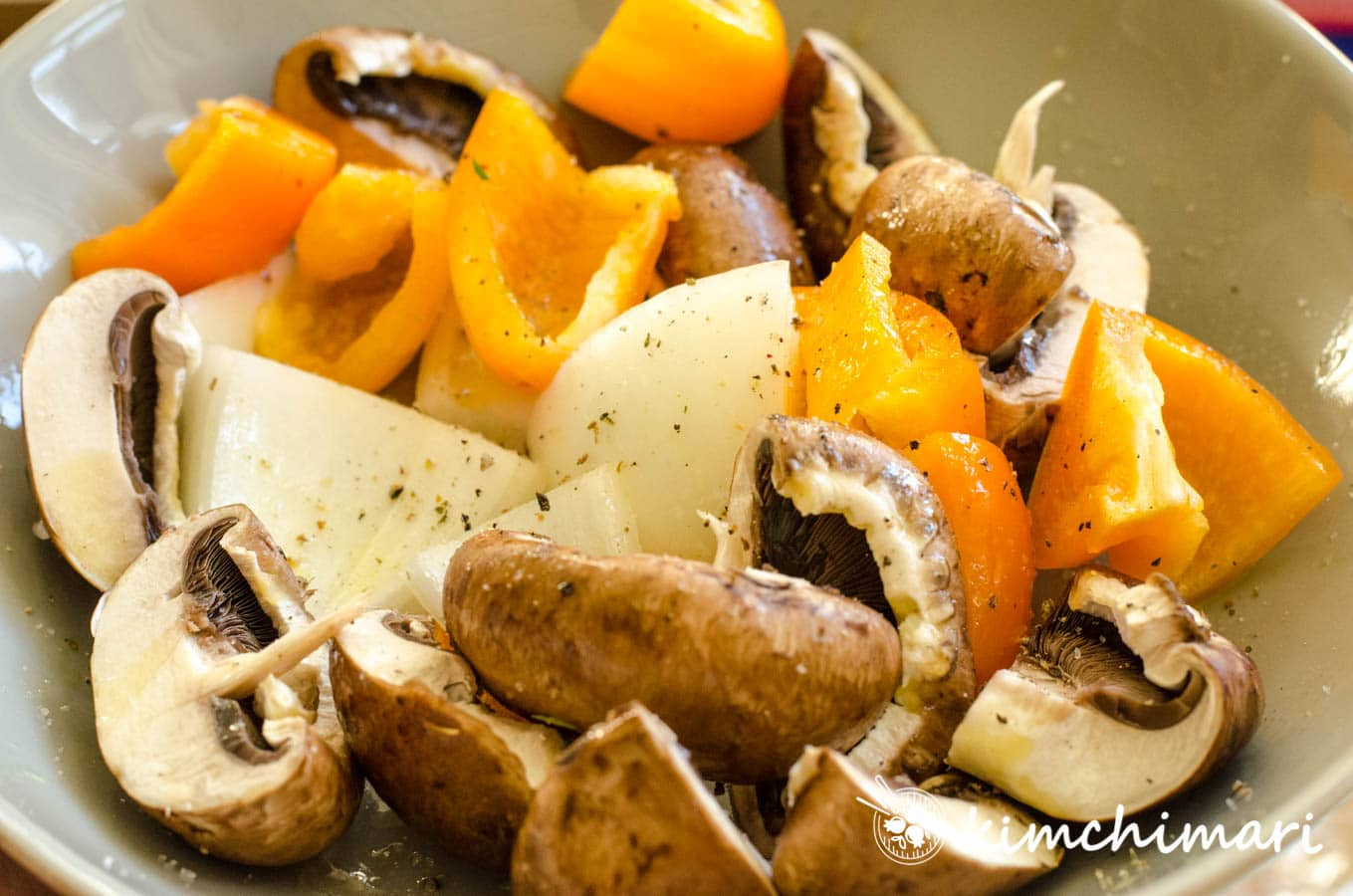 cut white mushrooms, bell peppers, onions in bowl