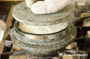 stone pot lid being opened with rice peeking thru between the lid and pot