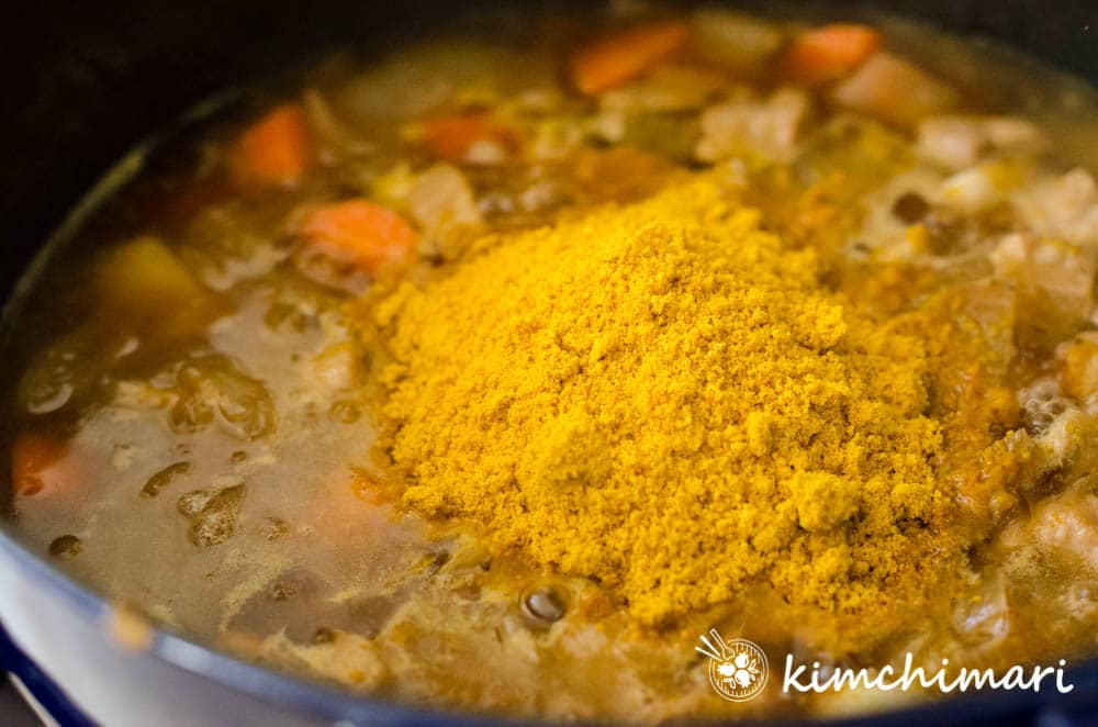 korean curry mix added to pot with cooked vegetables and meat in broth
