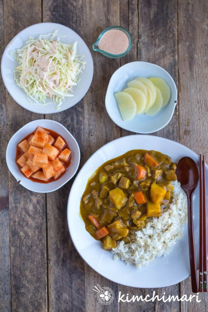 top view of korean curry rice served with side dishes of kkakdugi, danmuji and cabbage salad