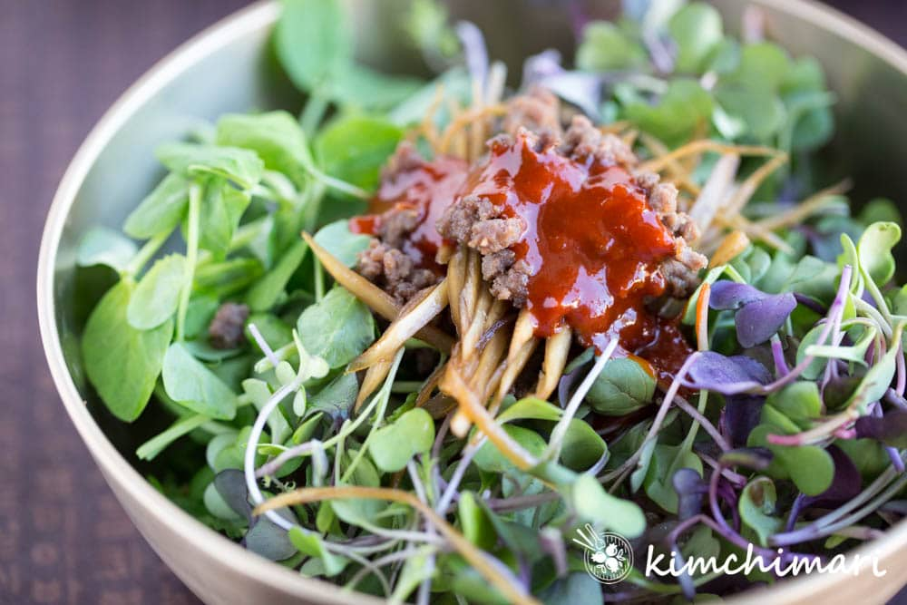 closeup of microgreens on rice, topped with beef and burdock roots and gochujang sauce in a brass bowl