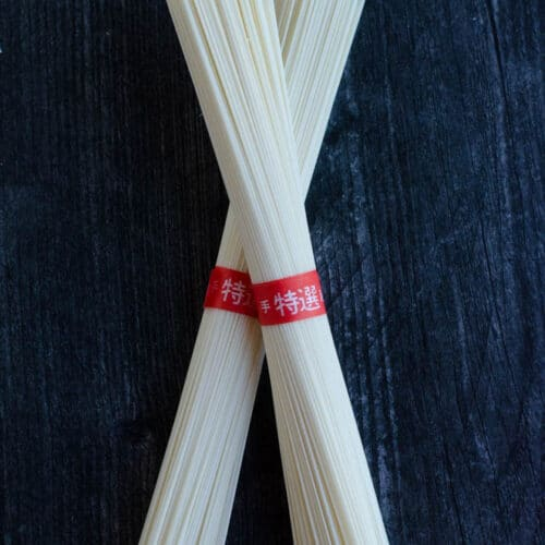 2 bunches of dried thin wheat noodles or somyeon on black background