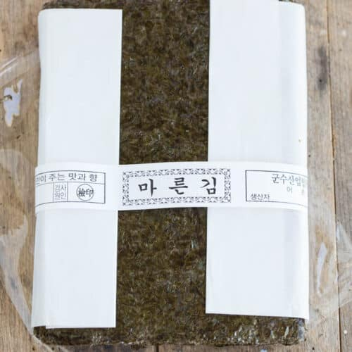 a whole bundle of Korean laver wrapped in paper tie on table